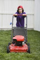 Mixed Race boy pushing lawn mower