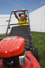 Mixed Race girl pushing lawn mower