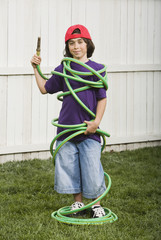 Mixed Race boy wrapped in garden hose