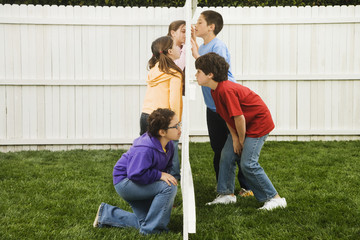 Mixed Race children looking at each other through fence
