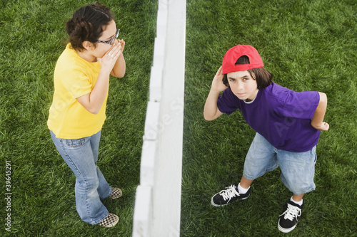 Mixed Race girl yelling to boy through fence