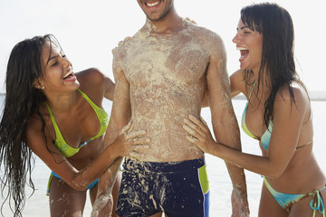 Two women rubbing sand on man at beach