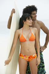 South American couple holding surfboard