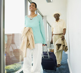 Senior African couple wheeling suitcases in hotel