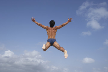 South American man in bathing suit jumping