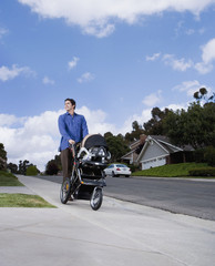 Hispanic man pushing baby stroller