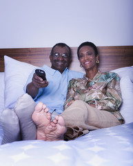 Senior African couple watching television in bed