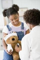 African American female doctor examining girl's teddy bear