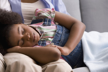 African American girl sleeping on mother's lap