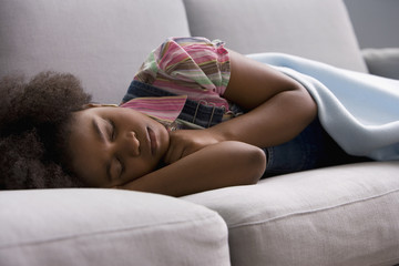 African American girl sleeping on sofa