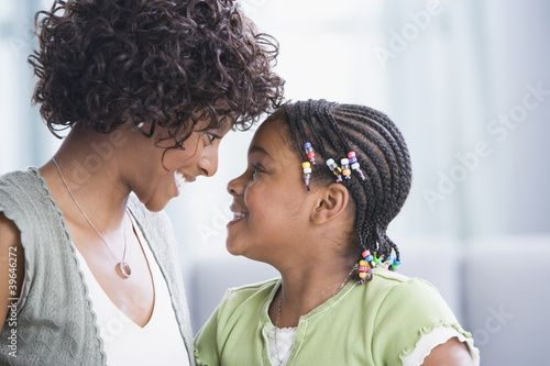 African American mother and daughter smiling at each other