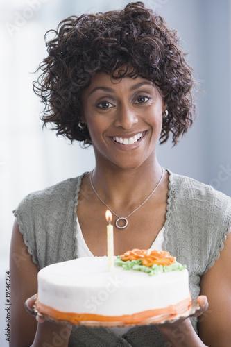 African American woman holding birthday cake