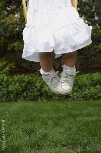 Hispanic girl jumping on grass