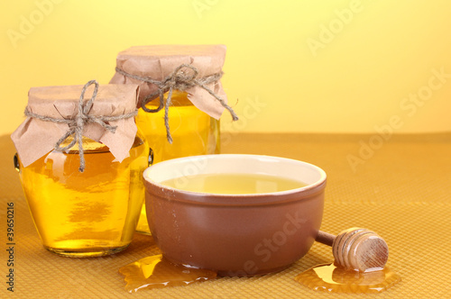 Jars of honey, bowl and wooden drizzler with honey
