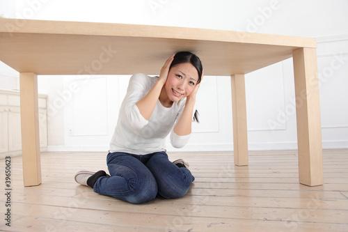 机の下に隠れる女性