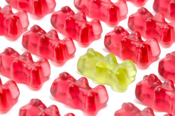Green gummy bear among red