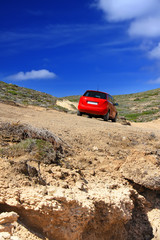 The car on a dirt road on a mountain slope. Greece. Rhodes..