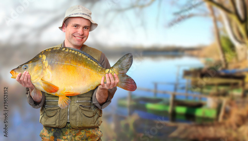 The fisherman with his big Carp at a beautiful lake.