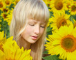 Relaxing girl among sunflower field
