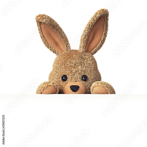 Leinwandbild Motiv Stuffed bunny peeking behind blank board - horizontal