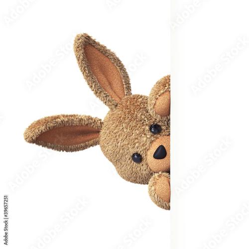 Leinwandbild Motiv Stuffed bunny peeking behind blank board - upright