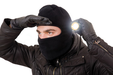 Thief with flashlight isolated in white