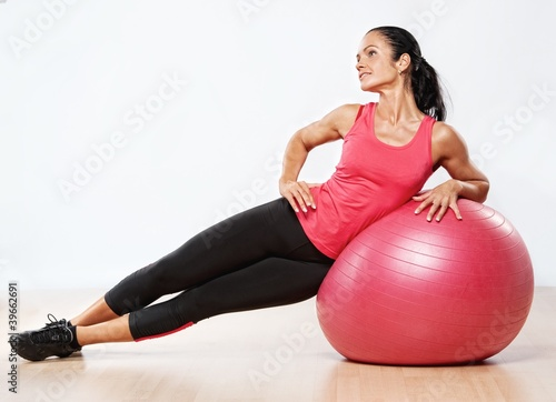 Beautiful athlete woman with a fitness ball.