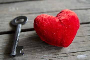 Heart and key on an old wooden surface.