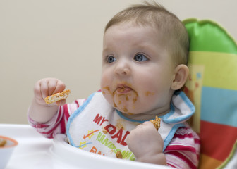 Nine month old baby learning to feed herself.