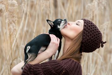 frau mit chihuahua hund knutschend im feld