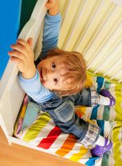 Happy kid hands on bed
