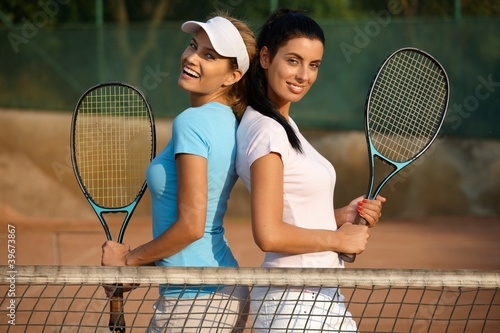 Pretty girls posing on tennis court smiling