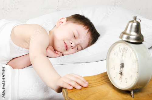 Boy 4 years sleeping bed old alarm clock brick wall
