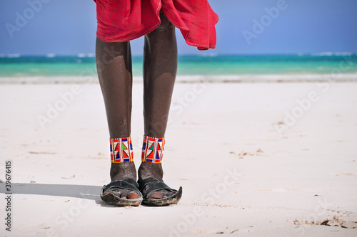 Feet and shoes Maasai on the ocean beach