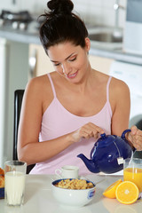 Jeune femme se servant un thé au petit déjeuner