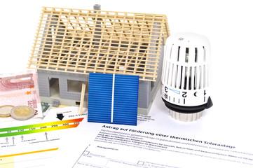 Haus im Bau mit Solarzelle, Energieausweis und Thermostat