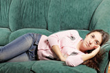 Brunette laying down on green sofa