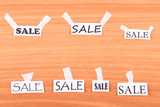 Pieces of paper with the words SALE glued to the wall poster