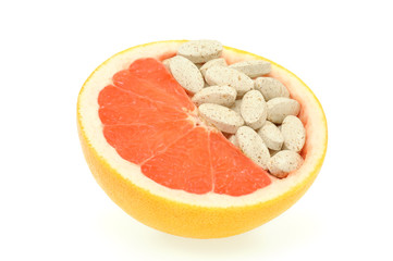 Close up of red grapefruit and pills isolated - vitamin concept