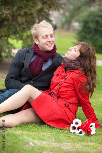 Happy couple in love having a date and sitting on the grass
