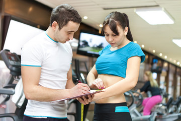 young girl with professional trainer  in gym