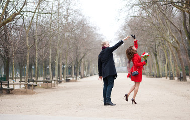 Happy couple dancing in the Luxembourg garden of Paris