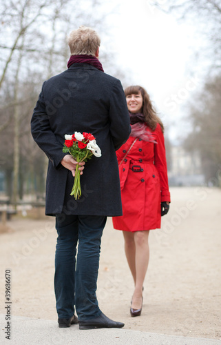 Happy couple having a date, man is going to offer flowers to his
