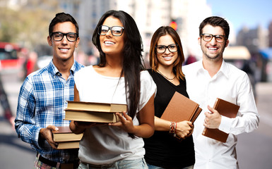 portrait of young students holding books at street