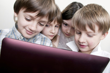group of children friends playing computer games