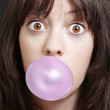young girl with a pink bubble of chewing gum against a black bac