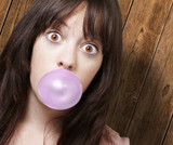 young girl with a pink bubble of chewing gum against a wooden ba
