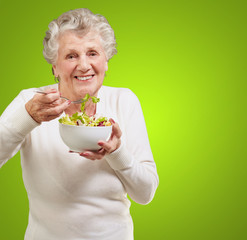 portrait of senior woman eating a fresh salad over green backgro