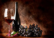 Vino rosso con grappolo di uva nera