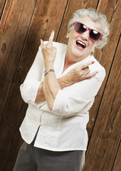 portrait of senior woman doing rock symbol against a wooden wall